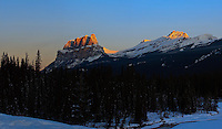 Castle Mountain is in the Rocky Mountains about half way between Banff and Lake Louise.  It is a very scenic spot that looks good in all sorts of light and weather conditions.  I love to see it when it is being lit up from the side because the shadows in between each of the parapet like peaks falls into deep shadow and makes the mountain look even more rugged than normal.  ..We were passing by at just the right time the other day to enjoy the sunrise.  It was a particularly beautiful thing when the Alpenglow dropped down the face of the mountain.  I love the Rockies!..©2010, Sean Phillips.http://www.Sean-Phillips.com