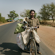 Umesh, a recycler from Uttar Pradesh, approaching Delhi. He uses his bicycle for carrying the trash that he picks up along the road. He sits on his cycle when the road goes downhill, otherwise he walks beside it.<br /> Utta Pradesh Province.