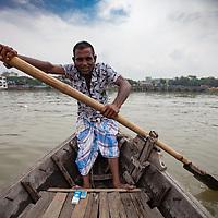 A ferryman rows a boat across the Buriganga river in Dhaka, Bangladesh