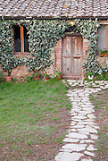 A stone walkway leads the way to an old home in Italy