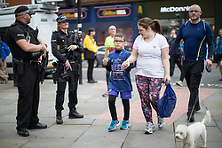 © Licensed to London News Pictures . 28/05/2017 . Manchester , UK . Armed police watch over the run . The Great Manchester Run 2017 . Security is still heightened in Manchester following a murderous bomb attack at an Ariana Grande gig at Manchester Arena on Monday 22nd May . Photo credit : Joel Goodman/LNP