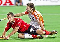 NEW DELHI - Rogier Hofman brengt de stand op 5-0, vrijdag tijdens de poulewedstrijd Nederland-Canada (6-0) bij het WK Hockey 2010 voor mannen in New Delhi. De Canadees Scott Sandison heeft het nakijken.