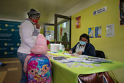 """Nurse Vivienne Wese screens patients for TB and COVID-19 as they arrive, today when the City of Cape Town opened a clinic extension in the Elsies River Library, to serve mothers and children with routine visits such as family planning and immunizations, Monday, July 13, 2020. Clinic extensions are being constructed to separate COVID-19 treatment and diagnosis from other treatments. """"I am [scared]."""" But it's the profession I chose, so I must do my job,"""" she says with a smile. She'll work on a rotation, one week on, and one week off, she explains. PHOTO: EVA-LOTTA JANSSON"""