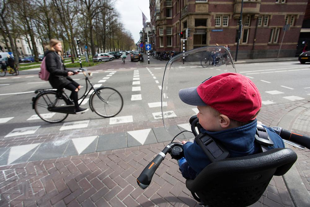 In Utrecht fietst een vader met een jongetje voorop in een kinderzitje door de stad.<br /> <br /> In Utrecht a father is cycling with his son in a child seat at the front.