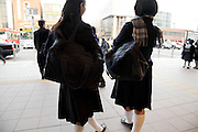 two teenaged female Japanese students in school uniform waiting