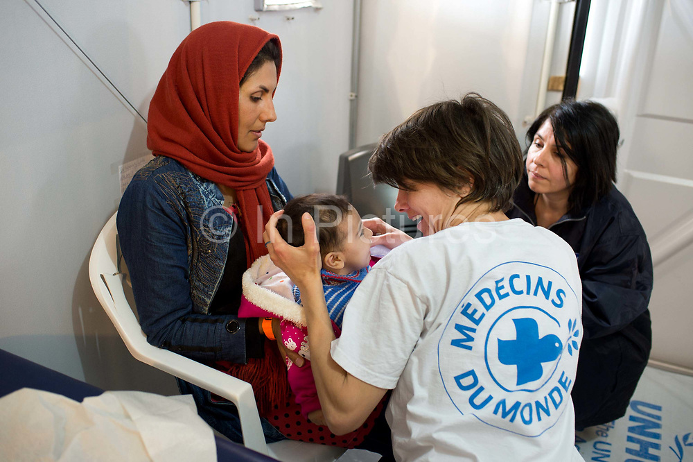 Greece with Doctors of the World (Medecins du monde). Chios Island, one of the places where refugees from Turkey land en route to Northern Europe. Souda camp. British Dr Sophie Quinney examines baby Sabina with help of translator Simi.