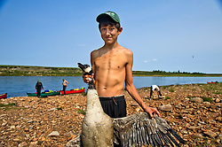 "Brendan Felix Head, 14, prepares to de-feather a duck in The Thelon, the largest and most remote game sanctuary in North America, which almost no one has heard of.  For the Akaitcho Dene, the Upper Thelon River is ""the place where God began.""  Sparsely populated, today few make it into the Thelon. Distances are simply too far, modern vehicles too expensive and unreliable. For the Dene youth, faced with the pressures of a western world, the ties that bind the people and their way of life to the land are even more tenuous. Every impending mine, road, and dam construction threatens to sever these connections. In July and August, 2011 a group of youth paddled to their ancestral hunting ground and spiritual abode.  this next generation of young leaders will be the ones who will need to speak for the Thelon the loudest. (Photo by Ami Vitale)"