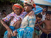 06 NOVEMBER 2014 - SITTWE, RAKHINE, MYANMAR: MOSLOBA HATU, 60, who suffers from multiple illnesses, is carried back to her home in an IDP camp for Rohingya Muslims near Sittwe. After sectarian violence devastated Rohingya communities and left hundreds of Rohingya dead in 2012, the government of Myanmar forced more than 140,000 Rohingya Muslims who used to live in and around Sittwe, Myanmar, into squalid Internal Displaced Persons camps. The government says the Rohingya are not Burmese citizens, that they are illegal immigrants from Bangladesh. The Bangladesh government says the Rohingya are Burmese and the Rohingya insist that they have lived in Burma for generations. The camps are about 20 minutes from Sittwe but the Rohingya who live in the camps are not allowed to leave without government permission. They are not allowed to work outside the camps, they are not allowed to go to Sittwe to use the hospital, go to school or do business. The camps have no electricity. Water is delivered through community wells. There are small schools funded by NOGs in the camps and a few private clinics but medical care is costly and not reliable.   PHOTO BY JACK KURTZ