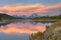 Orange clouds and Mount Moran reflected in still waters of the Snake River at Oxbow Bend at sunrise, Grand Teton National Park Wyoming