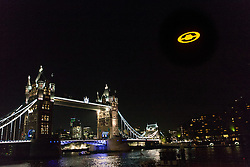 "© Licensed to London News Pictures. 05/11/2012. London, UK. A giant illuminated ""Halo 4"" Glyph symbol hovers over Tower Bridge in London on 5 November 2012. xBox 360 took over London's skies to launch the blockbuster ""Halo 4"". The ""Halo 4"" structure was suspended from a helicopter flying over the River Thames and measures 50 feet in diameter and weighs over three tons. Photo credit : Vickie Flores/LNP"