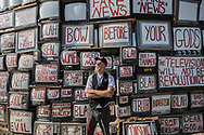 """Flip Cassidy painting his large """"Television Will Not Be Revolutionized"""" art piece.<br /> East Jesus, a privately owned artist colony and sculpture garden located inside Slab City.<br /> Slab City and the local environs."""