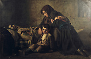 The Poor Man's Death' c1850s. Jean Pierre Alexandre Antigna (1817-1878) French Realist painter.  Body of pauper lies  a mattress on the floor, his grieving widow and children huddle together beside him.