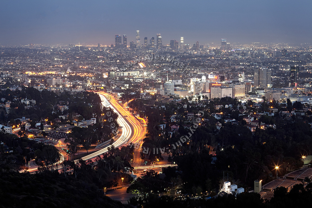 Downtown Los Angeles, lighting up after sunset, is visible in its grandeur from viewpoint along Mulholland Drive, California, USA.