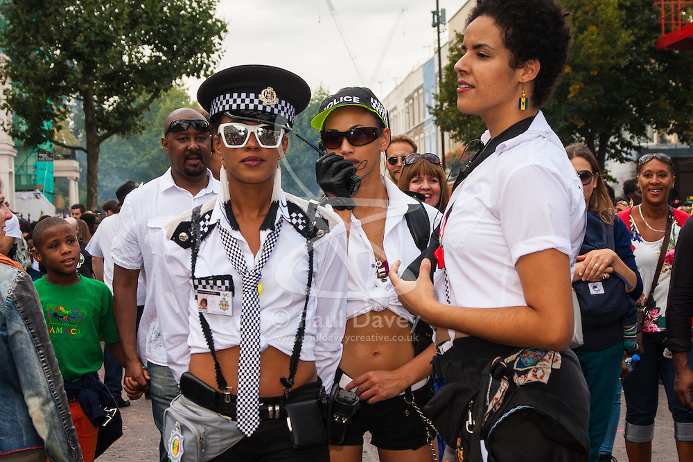 """London, August 24th 2014. """"Officers"""" from the """"Soca Police"""" ensure revellers keep dancing as thousands of Londoners of all races and cultures attend Notting Hill Carnival's """"Family friendly"""" day ahead of the main carnival on August Bank Holiday Monday."""