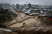 Rohingya refugees shield from the rain in Balukhali, Camp 10, part of the refugee camp sheltering over 800,000 Rohingya refugees, Cox's Bazar, Bangladesh, June 12, 2018. Bangladesh suffers intense cyclonic storms and some of the most intense monsoon rains on earth.