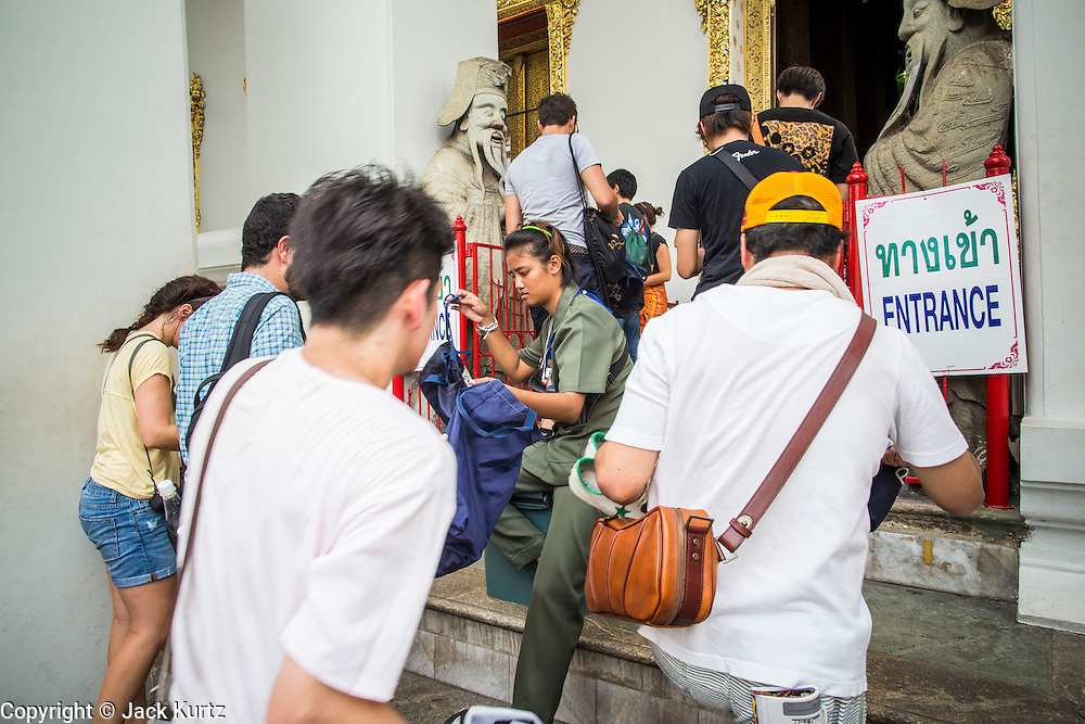26 NOVEMBER 2012 - BANGKOK, THAILAND:  Tourists are asked to take off their shoes by a temple employee before entering the hall housing the Reclining Buddha at Wat Pho in Bangkok. Thailand's Temple of the Reclining Buddha has gained further global prominence following a 45-minute tour by U.S. President Barack Obama and Secretary of State Hillary Clinton during their November 18-19 visit to the kingdom. Known also as the Temple of the Reclining Buddha, its official name is Wat Phra Chettuphon Wimon Mangkhlaram Ratchaworamahawihan. The temple is also known as the birthplace of traditional Thai massage. There is a popular massage school on the temple grounds.    PHOTO BY JACK KURTZ