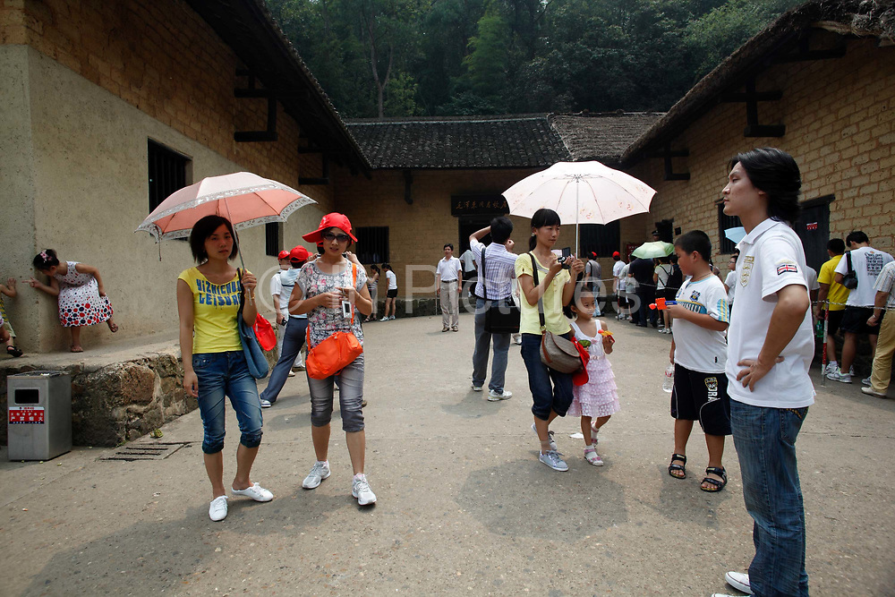 Visitors outside of  Mao's birthplace in Shaoshan, Hunan Province, China on 12 August 2009.  The village of Shaoshan, in rural Hunan Province, is tiny in size but big in name. It was the childhood home for Mao Zedong, the controversial revolutionary who came from obscurity but eventually defied all odds conquered China in the name of communism. Now his home, a sacred place among China's official propaganda, is in reality a microcosm of the country itself: part commercialism, part superstition, with a dash of communist ideological flavor.