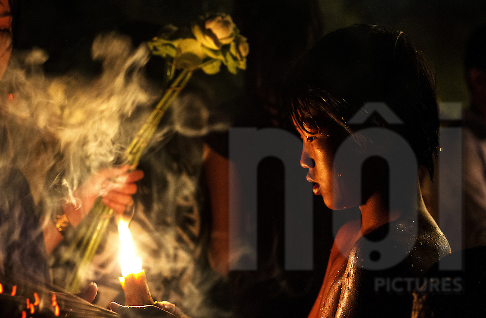 A young Khmer boy holds a candle for people to light their incense sticks to be used in prayer, Phnom Penh, Cambodia, Southeast Asia