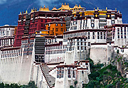 The Potala Palace in Lhasa dwarfs two pilgrims ascending the front staircase. Once the seat of the Tibetan government and the winter residence of the Dalai Lamas.
