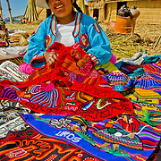 Colorful locals offer crafts for sale on the Uros Islands in Lake Titicaca, Peru.