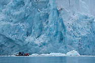 Ecotourism group in Zodiac inflatable boat by the Smeerenburg glacier in Svalbard, Norway, Arctic