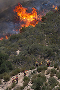 Firefighters work to extinguish a fire along a hillside, Friday May 31, 2013, near Castiac, California. Fourteen aircraft and more than 550 firefighter were deployed in a ground and air campaign against a brush fire that has blackened about 1,500 acres in sparsely populated San Francisquito Canyon in the Angeles National Forest northeast of Santa Clarita. The Powerhouse Fire, which broke out Thursday afternoon, was about 15 percent contained. The estimated date of full containment is Wednesday, June 5. (Photo by Ringo Chiu/PHOTOFORMULA.com)