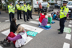 London, UK. 4 September, 2019. Metropolitan Police officers stand around anti-nuclear activists blocking a road outside ExCel London on the third day of a week-long carnival of resistance against DSEI, the world's largest arms fair. The third day's protests were organised by the Campaign for Nuclear Disarmament (CND) and Trident Ploughshares.