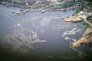 Oblique aerial view of logs floating on Rio Negro river and city of Manaus, Brazil 1962