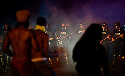 CMPD officers stand in a haze of tear gas as protestors approach on Old Concord Rd. on Tuesday night, Sept. 20, 2016 in Charlotte, N.C. The protest began on Old Concord Road at Bonnie Lane, where a Charlotte-Mecklenburg police officer fatally shot a man in the parking lot of The Village at College Downs apartment complex Tuesday afternoon. The man who died was identified late Tuesday as Keith Scott, 43, and the officer who fired the fatal shot was CMPD Officer Brentley Vinson. Photo by Jeff Siner/Charlotte Observer/TNS/ABACAPRESS.COM