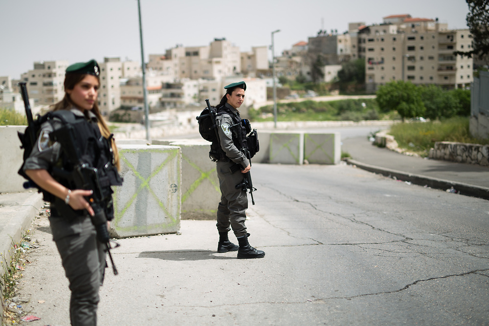 Israeli Border Police Women Corporal Mor Hadad (R) and  Staff Sergeant Chen Cohen (L) stand guard at the exit of the East Jerusalem neighborhood of Issawiya, in Jerusalem, Israel, on April 10, 2016.