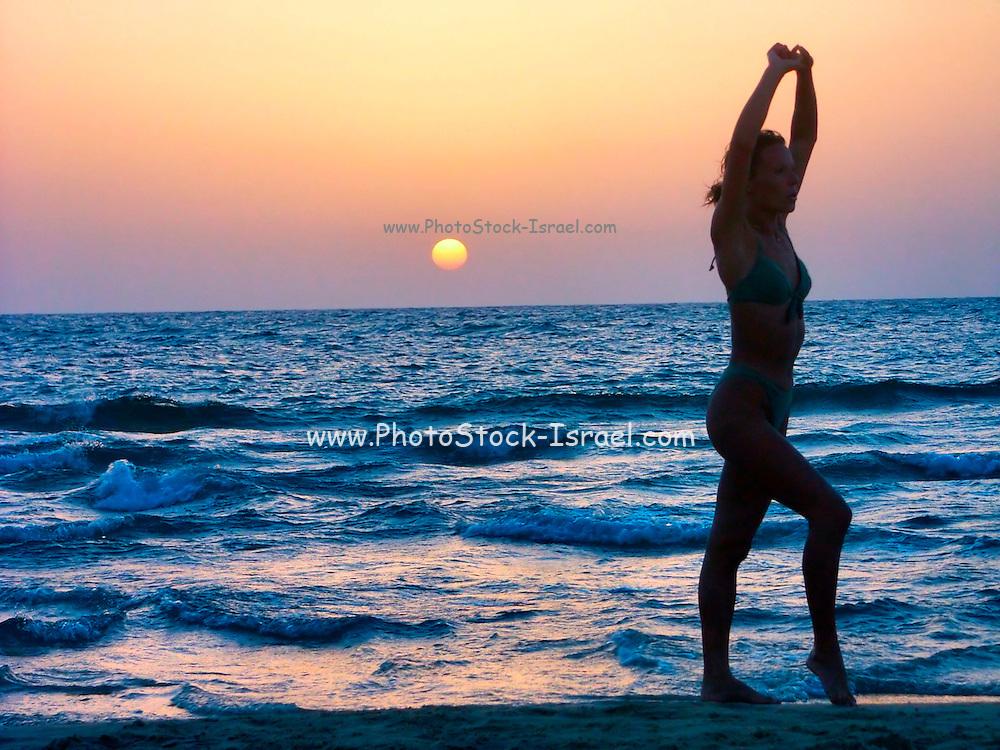 Israel Tel Aviv silhouette of a woman practising Gymnastics at sun set over the Mediterranean Sea