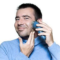 studio portrait on isolated background of a stubble man shaving electrique razor