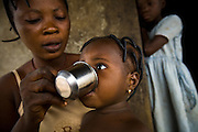 A woman gives her daughter a solution of water and crushed cotrimoxazole in the village of Lalo, Benin on Friday September 14, 2007.