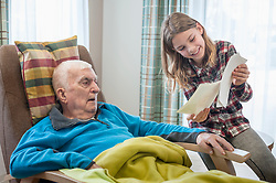 Granddaughter showing old photos to grandfather in rest home