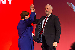 "© Licensed to London News Pictures. 24/09/2017. Brighton, UK. Leader of the Labour Party and MP for Islington North JEREMY CORBYN ""high fives"" MP for Islington South and Finsbury and Shadow First Secretary EMILY THORNBERRY at the end of her speech at the 2017 Labour Party Conference in Brighton. Photo credit: Hugo Michiels/LNP"