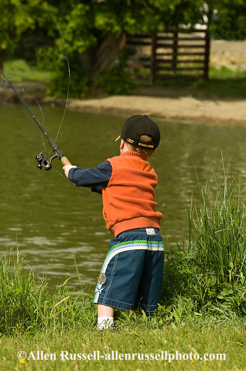 Young boy tries to fish at Kids Trout Derby, Sacajawea Park Lagoon, Livingston, Montana