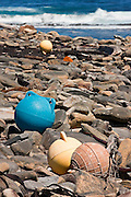 Plastic fishing floats and other flotsam lie on a boulder strewn beach in the Falkland Islands