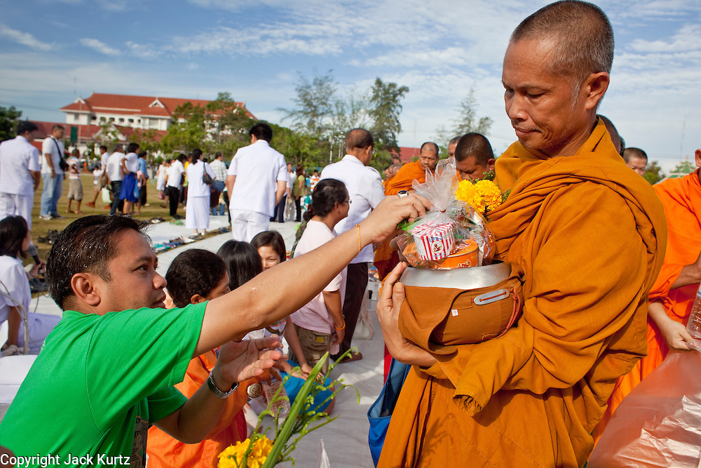 """Sept. 26, 2009 -- PATTANI, THAILAND:  A man donates food to a Buddhist monk during the Tak Bat Sankatan ceremony in Pattani, Thailand, Saturday. Buddhists in Thailand's three southern most provinces gathered in Pattani Saturday, Sept 26 to celebrate Tak Bat Sankatan, the day Lord Buddha returned to earth and was greeted by a crawd of his disciples and Buddhist believers who were waiting to offer him food. Buddhists monks representing the 266 """"Wats"""" (temples) in the three provinces (Pattani, Narathiwat and Yala) processed through the crowd and were presented with food and gifts.   Photo by Jack Kurtz"""