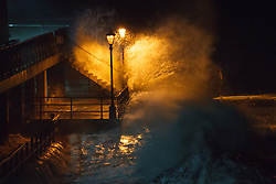 © Licensed to London News Pictures. 14/02/2014. Southsea, Hampshire, UK. A large wave crashes into two men risking their lives to pose for a photo in Old Portsmouth, Southsea, Hampshire, UK. Strong winds have battered the south coast, with hurricane force 12 winds being forecast. Photo credit : Rob Arnold/LNP