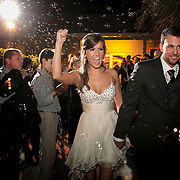 The bride and groom leave the wedding reception as bubbles are seen around them in Columbia. Photo by Columbia, SC wedding photographers Travis Bell ©Travis Bell Photography