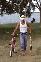 cowboy walking with a retro bicycle, fishing pole and fish from a lake and a woman with a dog