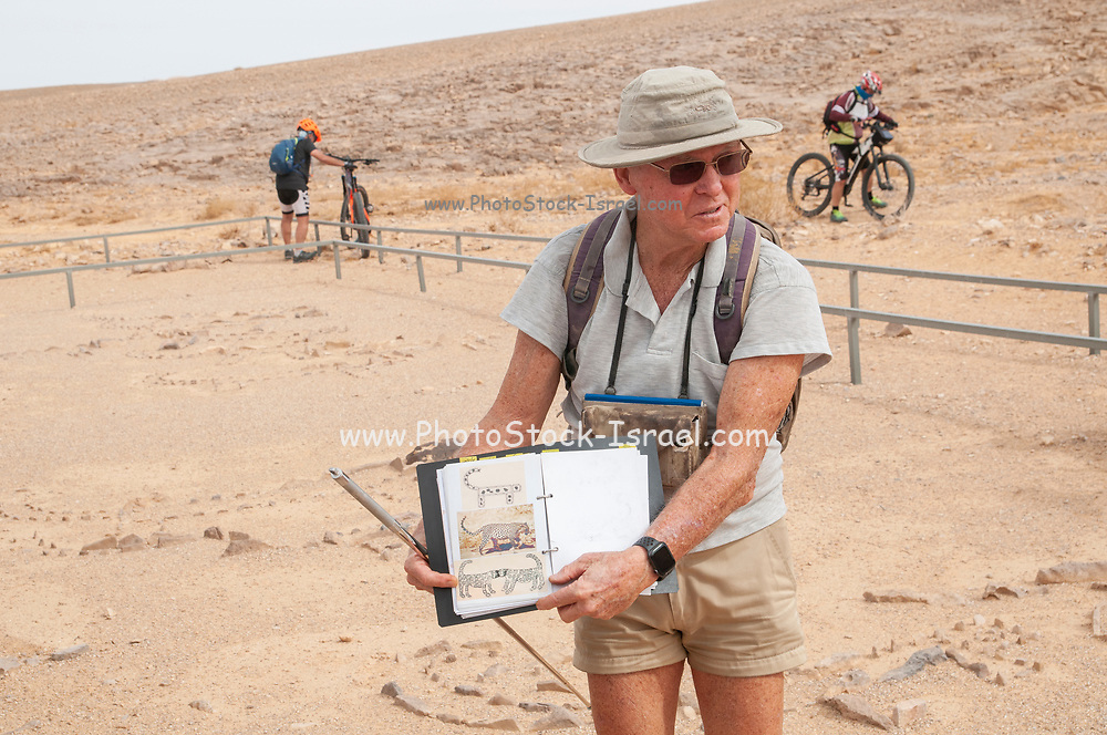 Archaeologist Dr. Uzi Avner explains his findings during the excavation of the site to a group at a prehistoric site in the Uvda valley desert region, Negev, Israel. These sites have been dates to have been dated to the Bronze age 6th–3rd Millennia BC