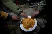 Typical evening oily rice served in a communal plate. Wakhi shepherd life inside the winter hut of Sap...Trekking up the Wakhan frozen river, the only way up to reach the high altitude Little Pamir plateau, home of the Afghan Kyrgyz community.