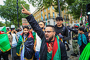 """Afghan men chant and gesture while carrying the Afghan national flag during a protest """"Save Afghanistan"""" outside Downing Street, Britain's PM Office in central London on Saturday, Aug 21, 2021. (VX Photo/ Vudi Xhymshiti)"""