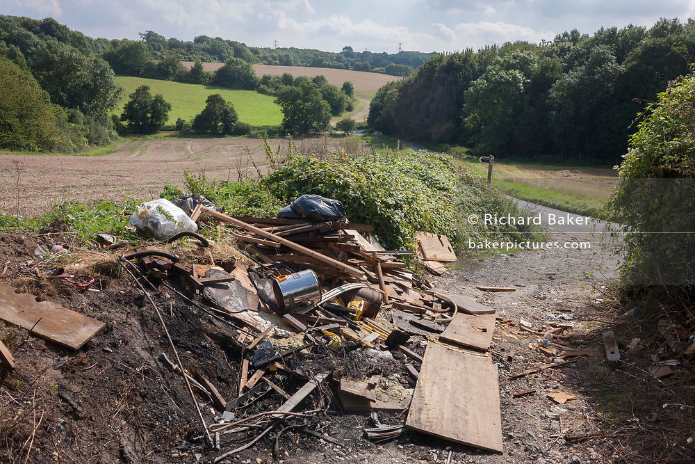 A heap of dumped, fly-tipped rubbish on a countryside footpath, on 27th August 2017, near Cobham, Kent, England.