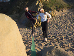 Teenage girl balancing along a slackline on a beach assisted by her sister