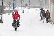 Een vrouw fietst op de Van Asch van Wijckkade in Utrecht door de sneeuw. Een jongen gooit op de achtergrond een sneeuwbal.<br /> <br /> A woman is cycling in the snow at the Van Asch van Wijckkade Utrecht.
