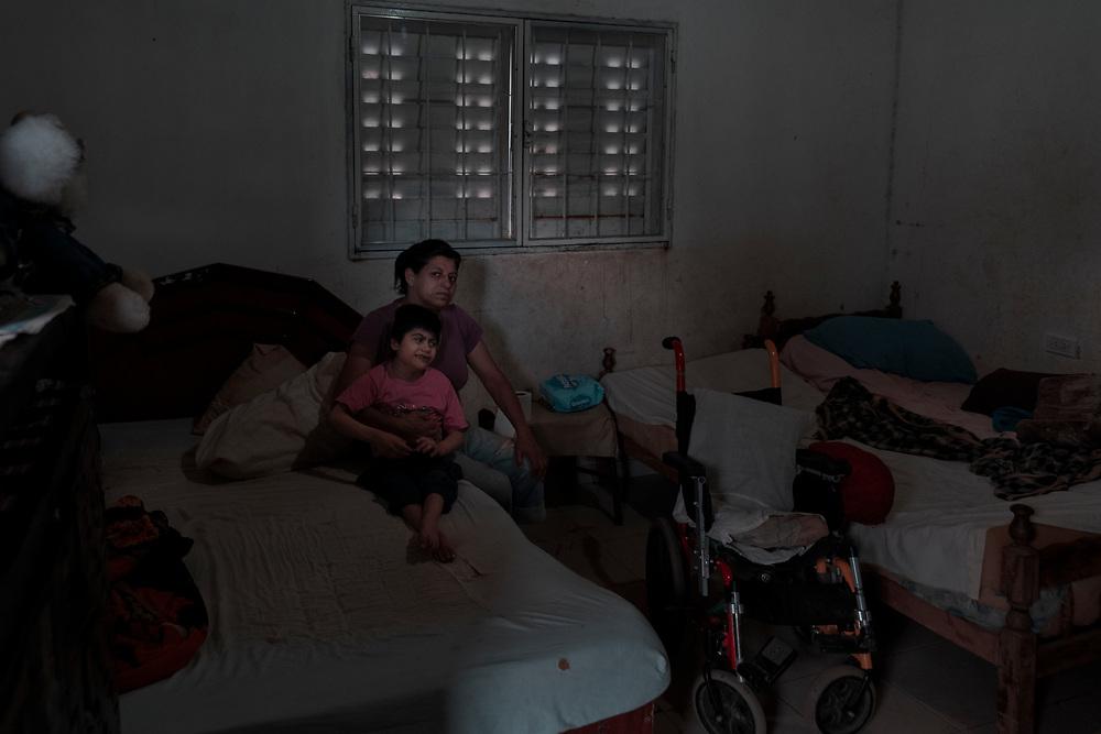 """Antonia (42) junto a su hija María Rosa (9). """"Ella nació así, yo no sé la razón. Ella no habla ni camina. Los Doctores nunca me dieron el motivo. María Rosa tiene el certificado de discapacidad que dice parálisis cerebral aguda pero nadie nos orienta. Yo soy la única que cuida de ella día y noche y así siempre"""" -Dice Antonia- María Rosa nunca recibió la pensión por discapacidad ni los tratamientos adecuados. Tampoco tuvo ningún tipo de escolarización especial. Su mundo se reduce a ser asistida y cuidada por su madre."""