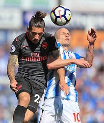 Arsenal's Hector Bellerin (left) and Huddersfield Town's Aaron Mooy battle for the ball during the Premier League match at the John Smith's Stadium, Huddersfield.