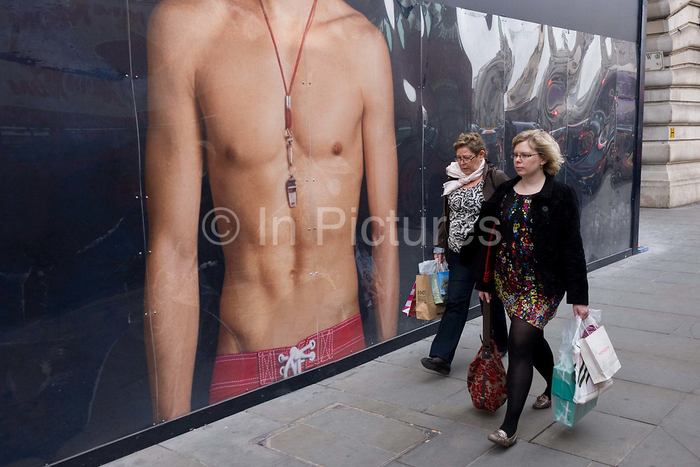 Women walk past a giant ad mural for Hollister California of a bare-chested young male model. The large image of the model wearing only swimwear and a whistle is seen to the full height of the billboard that obscures the construction site behind of the newest addition to the Regent Street clothing brand. The two rather plain looking women walk past without noticing the perfect male form whose torso with pectoral and abdominal muscles, perhaps more interested in getting home rather than admiring the young man above. This is a scene of handsome male youth, the perfect specimen displayed large and prominent for a female (or gay) audience.
